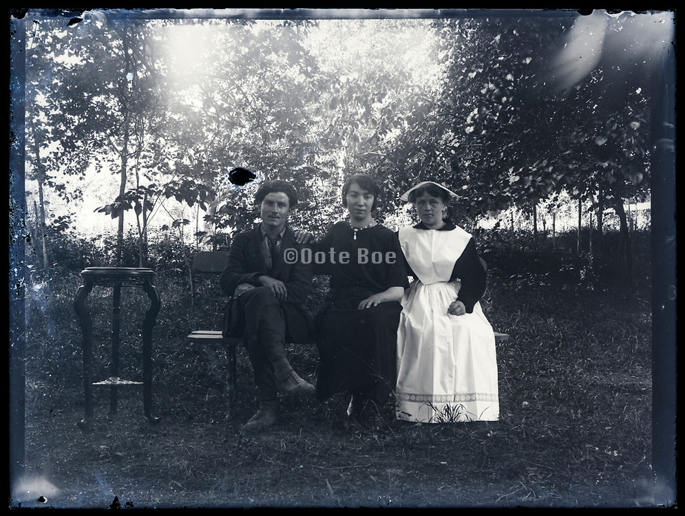 people in lush garden setting France ca 1920s