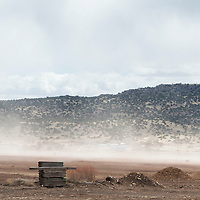 The high winds blow up sand and some saw dust  behind the Mount Taylor Millwork building in Milan Friday.