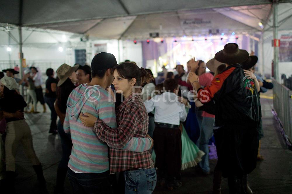 People dancing indoors at a Gaucho cowboy Rodeo, Flores de Cunha, Rio Grande do Sul.