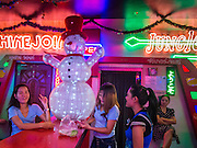 "17 DECEMBER 2013 - BANGKOK, THAILAND:    Workers in a ""go-go"" bar eat dinner in front of an illuminated snowman on Soi Cowboy in Bangkok.   PHOTO BY JACK KURTZ"