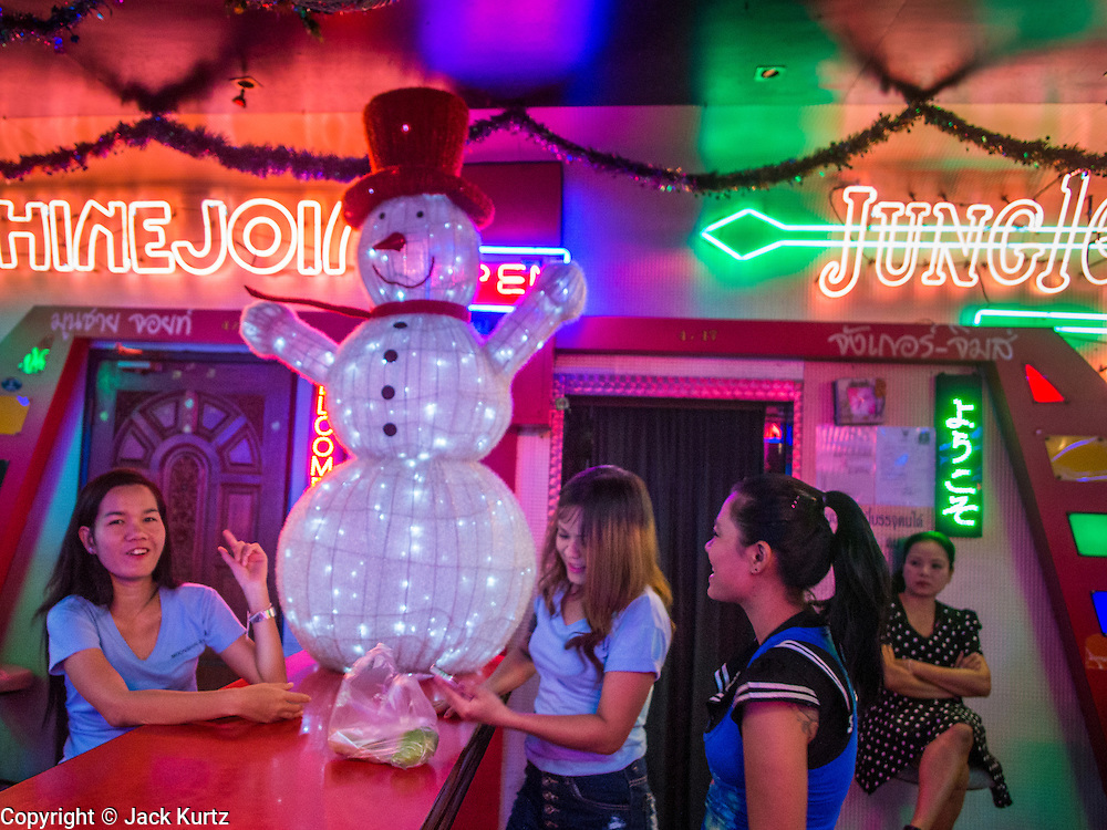 """17 DECEMBER 2013 - BANGKOK, THAILAND:    Workers in a """"go-go"""" bar eat dinner in front of an illuminated snowman on Soi Cowboy in Bangkok.   PHOTO BY JACK KURTZ"""