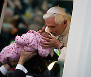 Pope Benedict XVI kisses a baby lifted up to his open car window as he arrives in his Popemobile. Greeted by crowds in Hyde Park during his papal tour of Britain 2010, the first visit by a pontiff since 1982. Taxpayers footed the £10m bill for non-religious elements, which largely angered a nation still reeling from the financial crisis. Pope Benedict XVI is the head of the biggest Christian denomination in the world, some one billion Roman Catholics, or one in six people. In Britain there are about five million Catholics but only a quarter of Catholics regularly attend Sunday Mass and some churches have closed owing to spending cuts.