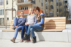 Three friends sitting on a bench in a playground, Munich, Bavaria, Germany