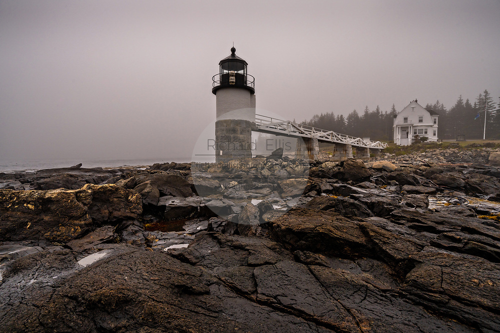 Fog descends over the Marshall Point Lighthouse near Port Clyde, Maine. The current lighthouse was built in 1832 on a rocky point of land near the mouth of Port Clyde Harbor and was featured in the major motion picture Forrest Gump.