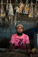 Cox's Bazar, Bangladesh - October 27, 2017: A Bangladeshi man sells smoked fish at a beachside stall in Cox's Bazar. The area is famous for its dried fish, which is sold locally as well as exported.