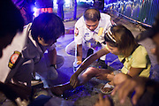 "02 OCTOBER 2009 -- BANGKOK, THAILAND: YOTHAPONG TAWATCHAI, center, a volunteer with Poh Teck Tung, tends to a woman and her son after they were hurt in a motorcycle accident. The 1,000 plus volunteers of the Poh Teck Tung Foundation are really Bangkok's first responders. Famous because they pick up the dead bodies after murders, traffic accidents, suicides and other unplanned, often violent deaths, they really do much more. Their medics respond to medical emergencies, from minor bumps and scrapes to major trauma. Their technicians respond to building collapses and traffic accidents with heavy equipment and the ""Jaws of Life"" and their divers respond to accidents in the rivers and khlongs of Bangkok. The organization was founded by Chinese immigrants in Bangkok in 1909. Their efforts include a hospital, college tuition for the poor and tsunami relief.   PHOTO BY JACK KURTZ"