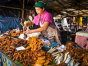 03 APRIL 2015 - CHIANG MAI, CHIANG MAI, THAILAND: A fried meat vendor bags a take away order for a customer in the market in Chiang Mai, Thailand.        PHOTO BY JACK KURTZ