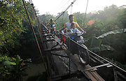CENTRAL JAVA, INDONESIA - APRIL 06:<br /> <br /> The children risking their lives on the way to school: Pupils use aqueduct just inches wide to avoid three-mile walk <br /> <br /> <br /> Children in Indonesia are risking their lives everyday just to get to school.<br /> They use an aqueduct, suspended hundreds of metres above the ground as a shortcut, even though it was not built for people to walk on.  <br /> It is meant to transport water, but the wooden structure links Suro Village and Plempungan Village in Java.<br /> <br /> Even though it is dangerous, they would rather use the precarious structure than walk a distance over three miles.  <br /> <br /> Children cycle along a wooden planks in the middle in their school uniform while local adults use it to transport food and material between the two villages. <br /> Earlier this year a group of Indonesian children were filmed crossing a collapsed suspension bridge over a swollen river to reach their school after three suspension bridges in the district of Lebak collapsed due to flooding. <br /> Despite the poor transport links the Indonesian island has a population of 137 million, meaning it is the world's most populous island, and one of the most densely-populated places on the globe.<br /> ©Exclusivepix Media