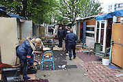French police walk through an empty Romanian Roma Gypsy squatter camp which will be destroyed today, after a mass eviction. Seine St Denis, Paris suburbs<br /><br />Roma Gypsies in Paris: Romanian Roma living in difficulty who have come to France looking for a better live, find themselves in a similiar predicament, facing racism from the general populus and systematic controls and evictions from their makeshift squatter camps in the suburbs and temporary places of abode inside Paris. Some recycle metal or suft through the rubbish bins looking for items to sell. Others beg or play music looking for handouts from passers by. Paris and Banlieu, Ile de France, France April 2014