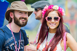 Early arrivals canenjoy the  blistering heat in sunglasses and fancy dress. The 2015 Glastonbury Festival, Worthy Farm, Glastonbury.