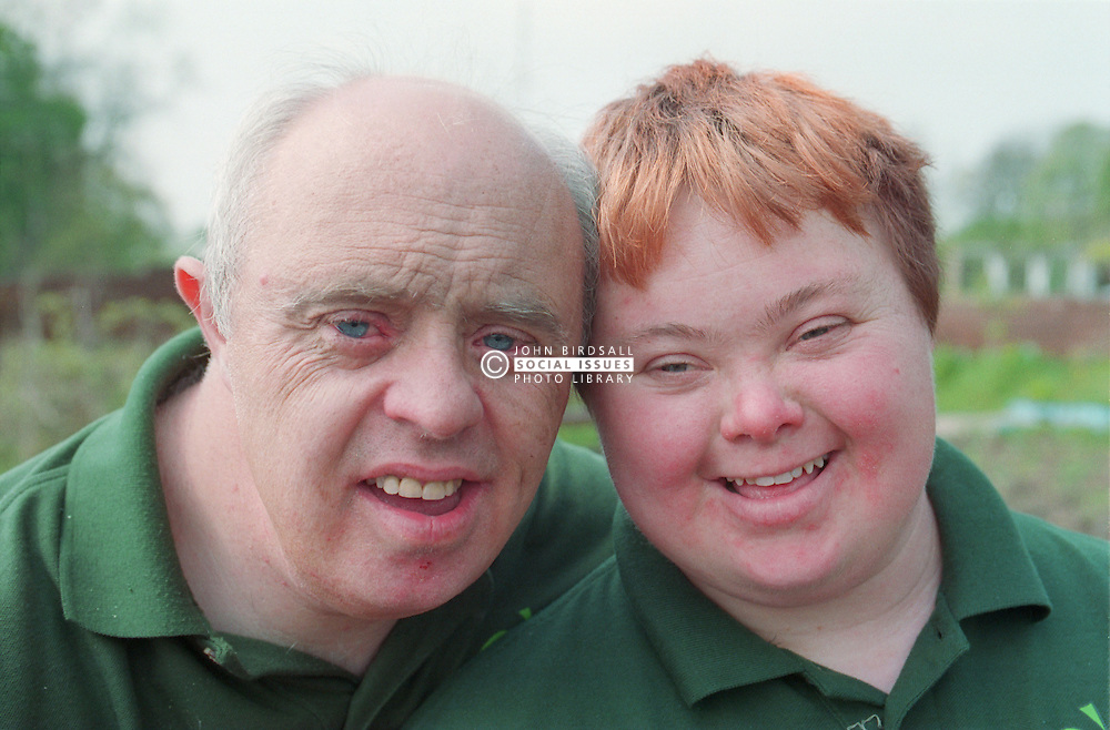 Portrait of man and woman with Downs Syndrome working on community allotment project,