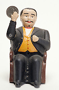 doll figure of man in suit waving money