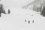 Three hikers snowshowing at Echo Lake in the Sierra Nevada, Eldorado National Forest, California