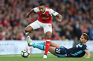 Theo Walcott of Arsenal leaps over Gaston Ramirez of Middlesbrough. Premier league match, Arsenal v Middlesbrough at the Emirates Stadium in London on Saturday 22nd October 2016.<br /> pic by John Patrick Fletcher, Andrew Orchard sports photography.