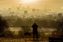 © Licensed to London News Pictures. 06/01/2017. London, UK. A man walks his dog whilst sunrise is seen over the city of London from Parliament Hill on Hampstead Heath in north London on a cold winter morning of Friday, 6 January 2016. Photo credit: Tolga Akmen/LNP