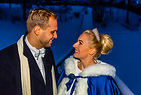 A Newlywed Norwegian couple pose for a photo on a cold winter evening after their wedding, Trysil, Norway.