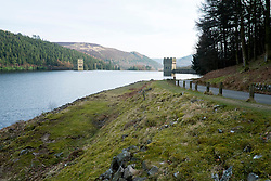 """Howden Reservoir in Derbyshire, England is Y shaped and the top one of three reservoirs in the Upper Derwent Valley, the middle reservoir being Derwent and the lower being Ladybower both to the south. Between them they provide practically all of Derbyshire's water, as well as a large part of South Yorkshire and as far afield as Nottingham and Leicester. The western side of the reservoir stands in Derbyshire, while the Eastern side is in Sheffield, South Yorkshire. The county border runs through the middle of the reservoir, following the original path of the River Derwent. <br /> Begun in on 16 July 1901 and completed in July 1912 its dam wall has the same neo-Gothic solid masonry dam wall, built from huge stones as the Derwent Reservoir. The Stone was transported along a specially created railway from the quarries at Grindleford. Over 1,000 workers lived in a specially constructed and self-contained town of Birchinlee also known as """"Tin Town"""".  The wall is 117ft (36m) tall, 1,080ft (330m) long, and  holds back 1,900,000 imperial gallons (8,600kl) of water collected from a catchment area of 5,155 acres (20.86km2).<br /> 22  March 2015 Image © Paul David Drabble www.pauldaviddrabble.co.uk"""