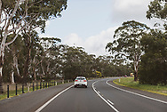 View through a vehicle windshield while driving on a two-lane highway outside Ballarat in Victoria State, Australia