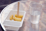 plastic basket with some French fries and cup with water