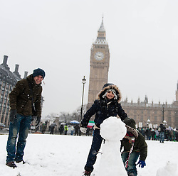 © Licensed to London News Pictures. 20/01/2013. London, UK. Children  and their father play in the snow in Parliament Square, central London. Photo credit : Richard Isaac/LNP