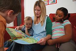 Nursery nurse reading book with children