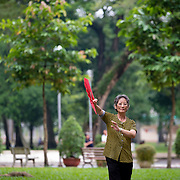 Woman practicing thai chi with fan in Tao Dan Park, Saigon