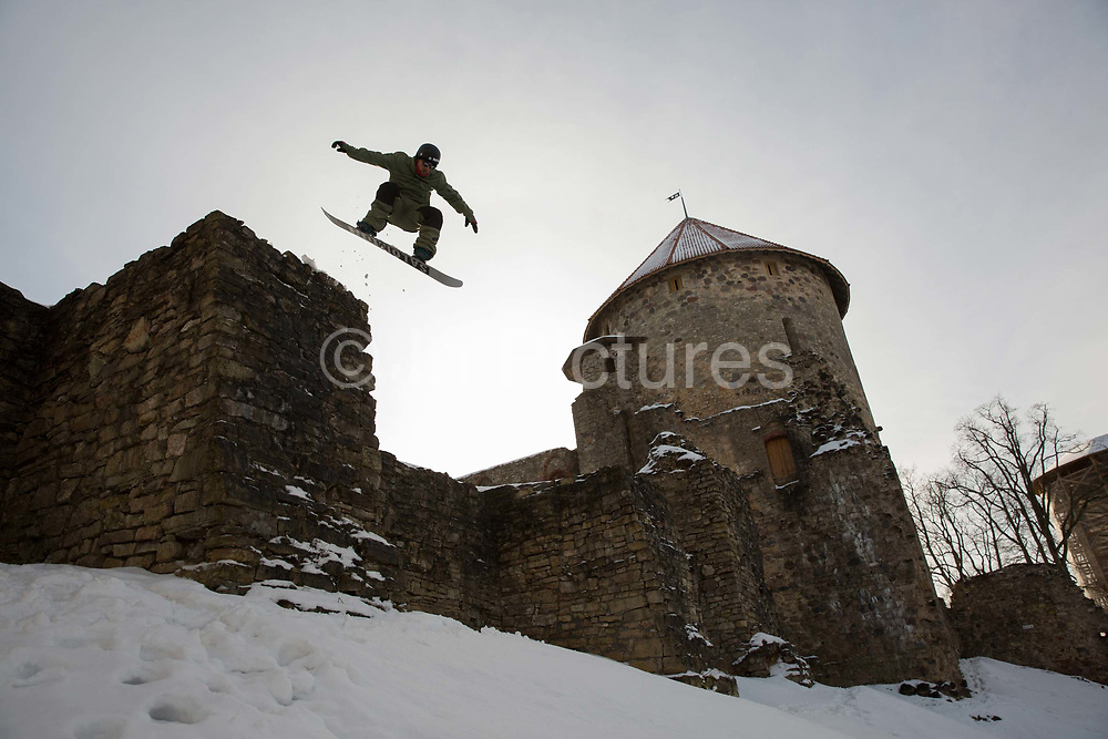 A male snowboarder jumps from a wall of the historic 13th century castle on the 14th February 2019 in Cesis in Latvia. Cesis is a town in north eastern Latvia, known for its medieval castle.