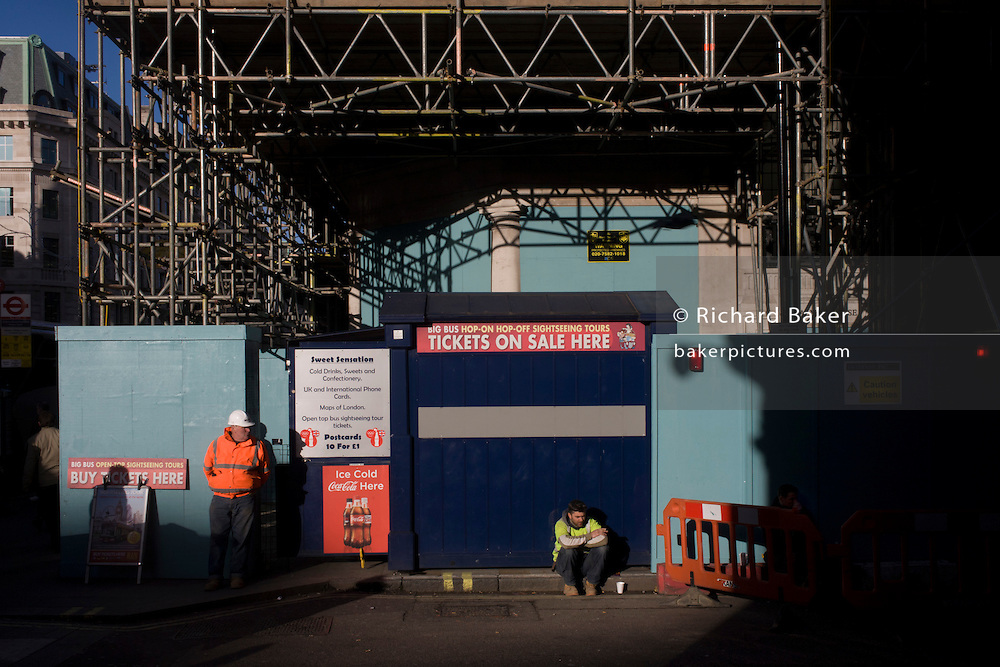 Construction workers taking a lunchtime break on a central London street corner.