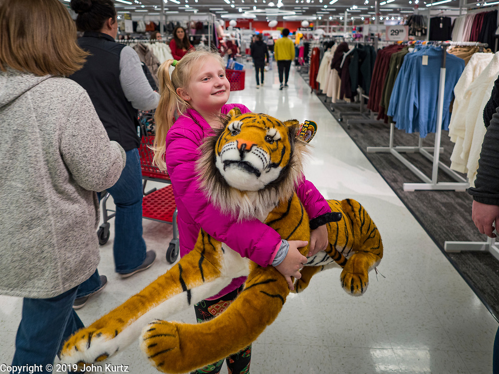 """28 NOVEMBER 2019 - ANKENY, IOWA: ELLIE VERSTEEG (VerSteeg), 8, from Ankeny, IA, carries a plush tiger toy she bought at the Target store in Ankeny, Iowa, Thursday evening. """"Black Friday"""" is the unofficial start of the Christmas holiday shopping season and has traditionally thought to be one of the busiest shopping days of the year. Brick and mortar retailers, like Target, are facing increased pressure from online retailers this year. Many retailers have started opening on Thanksgiving Day. Target stores across the country opened at 5PM on Thanksgiving to attract shoppers with early """"Black Friday"""" specials.     PHOTO BY JACK KURTZ"""