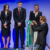 Waterpolo Olympic champion Tamas Kasas (2nd R) attaches a ribbon to the national flag of the Hungarian Olympic Committee during the swearing in ceremony of the Hungarian Olympic Team that will travel to London in Budapest, Hungary on June 22, 2012. ATTILA VOLGYI