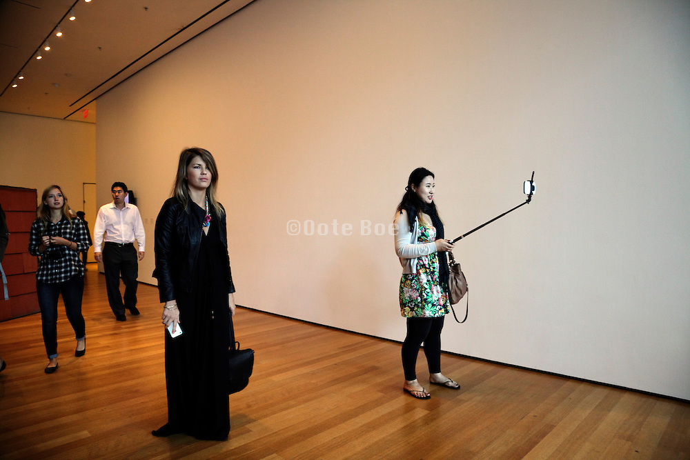 woman with a selfie stick inside the Museum of Modern Art, New York