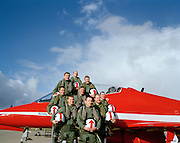 Nine pilots of the elite 'Red Arrows', Britain's prestigious Royal Air Force aerobatic team, stand in the shape of their signature 'Diamond Nine' formation with one of their Hawk jet aircraft at the team's headquarters at RAF Scampton, Lincolnshire. Today they have reached the all-important milestone of 'first 9-ship' (when all nine aircraft have flown a basic air show display together, after two groups have practiced seperately) and is the culmination of five months rigorous Winter training. They stand proud with beaming smiles on a warm spring day, their flying helmets with those famous arrows pointing towards blue sky and fluffy clouds. Still dressed in green flying suits, they go on to their spring training ground at Akrotiri, Cyprus where they earn the right to wear red suits, known around the world. At the front is team leader, Squadron Leader Spike Jepson...