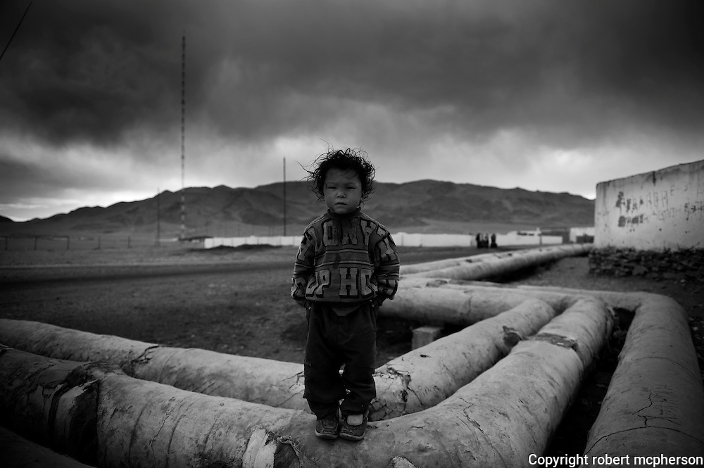 Mongolia(2008). Kazakh child standing on old pipes from the industry developed during communist era which is now out of function in Bayan Olgii.  ..Bayan Ulgii town is located in Mongolia`s western-most province. It is set in the Altai mountains where Mongolia,China and Russia converge. It is the only province where Mongolians are not the majority: about 90% of the population are ethnically Kazakh and practise Islamic traditions. Bayan Ulgii town suffered from the collapse of the socialist system; artificially created plants and industries buckled. Suddenly, all services and goods became very expensive. Today, Bayan Ulgii is the poorest province of Mongolia. Maternal and infant mortality rate is much higher than in the rest of the country and the central hospital still use Soviet made equipment waiting to be replaced.