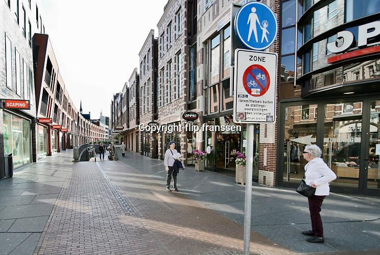 Nederland, Nijmegen, 6-4-2020 De binnenstad van Nijmegen is zo goed als leeg . Het is duidelijk rustiger en stiller in de straten, winkelstraten van het centrum in de stad . Mensen blijven thuis om zo min mogelijk risico te nemen ivm het corona virus . Terrassen zijn gesloten.Foto: Flip Franssen