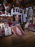 Mary Lee Begay showing two of her vegetable dye rugs in the Rug Room of Hubbell Trading Post, Hubbell Trading Post National Historic Site, Arizona.
