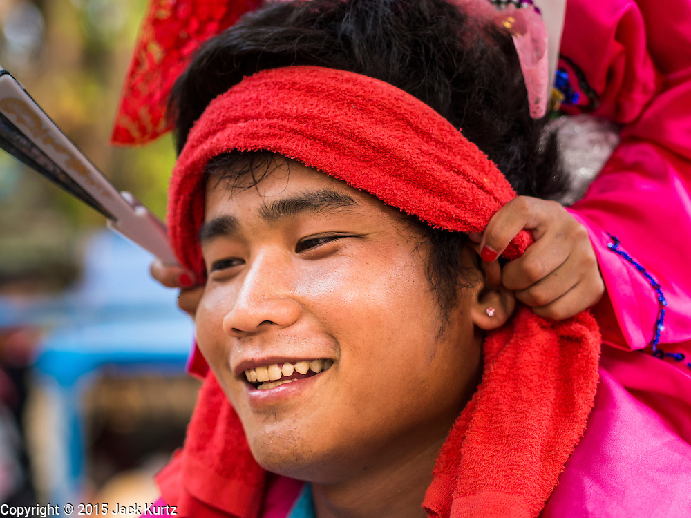 """05 APRIL 2015 - CHIANG MAI, CHIANG MAI, THAILAND: A Tai Yai man carries a Buddhist novice on his shoulders during the second day of the three day long Poi Song Long Festival in Chiang Mai. The Poi Sang Long Festival (also called Poy Sang Long) is an ordination ceremony for Tai (also and commonly called Shan, though they prefer Tai) boys in the Shan State of Myanmar (Burma) and in Shan communities in western Thailand. Most Tai boys go into the monastery as novice monks at some point between the ages of seven and fourteen. This year seven boys were ordained at the Poi Sang Long ceremony at Wat Pa Pao in Chiang Mai. Poy Song Long is Tai (Shan) for """"Festival of the Jewel (or Crystal) Sons.    PHOTO BY JACK KURTZ"""