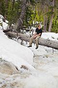 Charlie Bloch relaxes on a fallen log bridging a raging creek in Baker Gulch, Never Summer Wilderness, Colorado.