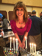 MARGARET BIEGELMAN, of Merrick, has four lighted candles in her menorah at the Merrick Jewish Centre attempt to regain the Guinness World's Record for Most Menorot Lit in One Place at One Time that the congregation held in 2011. On the third night of Hanukkah, the 'Light Up the Night 2 - Bringing the Record Home' event also included a ceremonial candle lighting in the main sanctuary. Though the Menorah Lighing goal to light at least 1,000 menorot was missed, and the record was not won back, over 600 menorot were lit at the MJC at one time.
