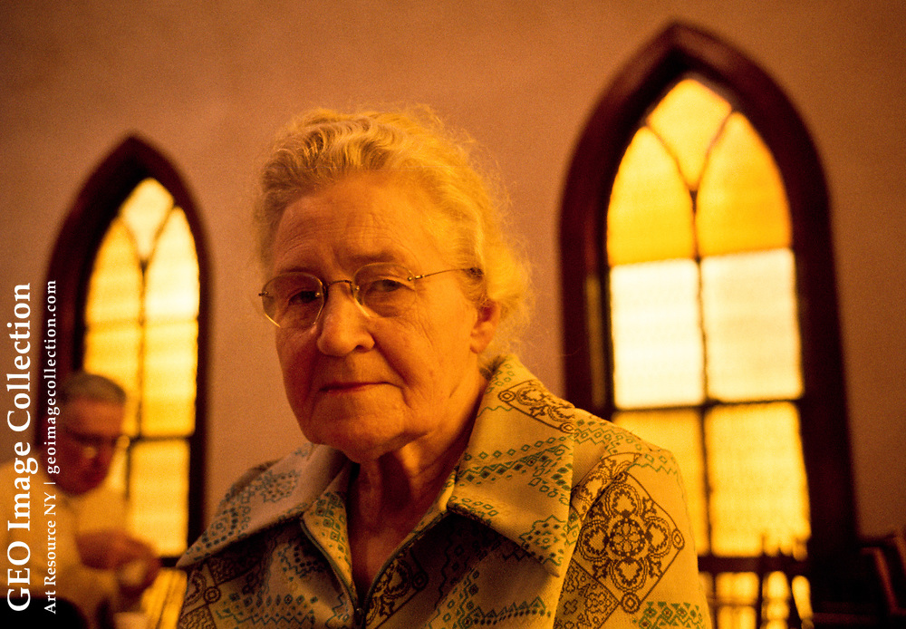Older woman sitting in the Minnesota City Baptist Church, built 1875. The church is built in Gothic Revival style with Gothic windows and yellow stained glass.