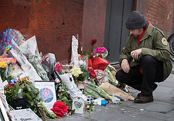 © Licensed to London News Pictures. 10/01/2017. London, UK. A fan looks at floral tributes at a mural and shrine to David Bowie in Brixton on the first anniversary of his death. David Bowie was born in Brixton, south London. Photo credit: Peter Macdiarmid/LNP