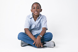 Young boy sitting on the floor crossed legged,