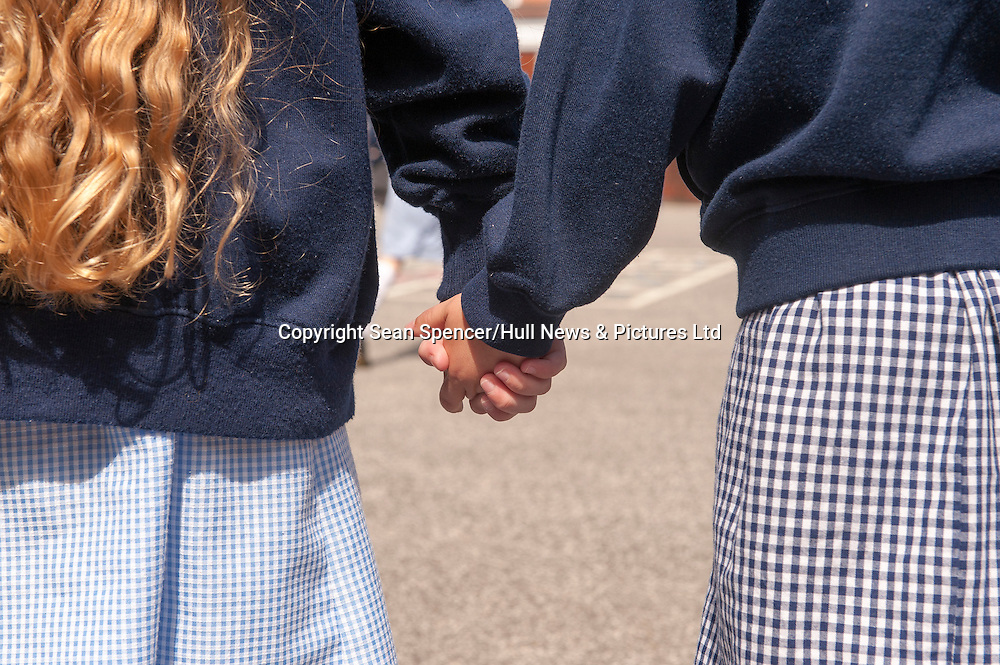 Two young girls in school uniform hold hands in the playground.