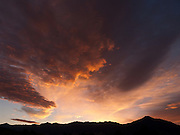 Sunset turns clouds orange and yellow set against a blue sky in Wyoming, USA.