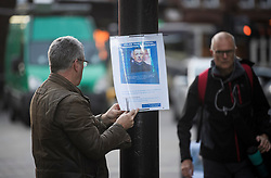 © Licensed to London News Pictures. 17/12/2018. London, UK.  A member of the Met Police places a notice explaining that facial recognition trials are taking place in the area as the Metropolitan police trial facial recognition technology on members of the public in central London. The surveillance software is being used overtly with a uniformed presence. Privacy campaigners have expressed concerns about the use of the technology. Photo credit: Ben Cawthra/LNP
