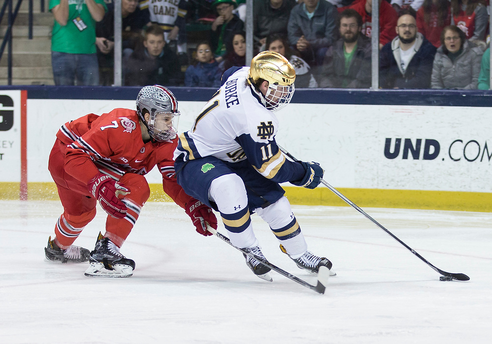 March 17, 2018:  Notre Dame forward Cal Burke (11) drives to the net with the puck as Ohio State defenseman Wyatt Ege (7) defends during NCAA Hockey game action between the Notre Dame Fighting Irish and the Ohio State Buckeyes at Compton Family Ice Arena in South Bend, Indiana.  Notre Dame defeated Ohio State 3-2 in overtime.  John Mersits/CSM