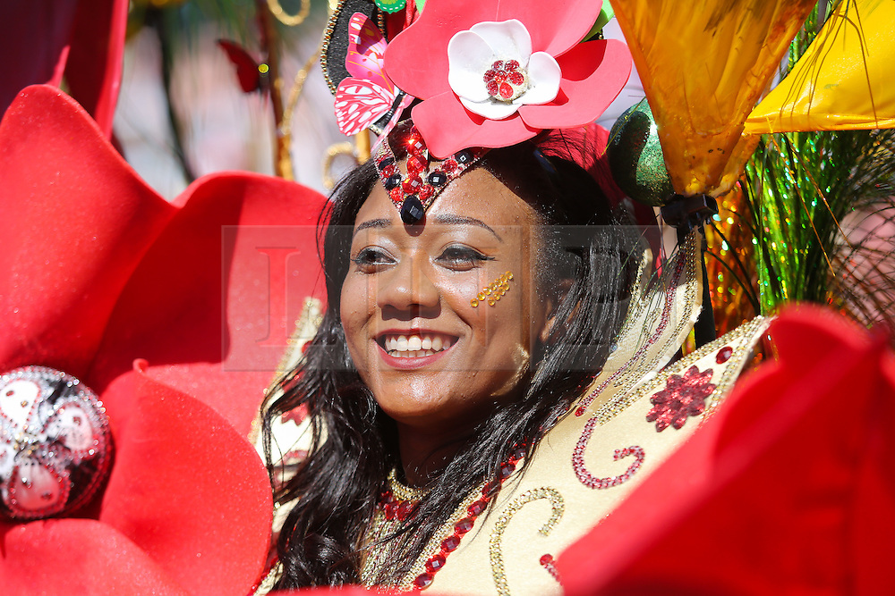© Licensed to London News Pictures. 29/08/2016. Leeds, UK. A woman smiles as she dances in her brightly coloured costume at the Leeds West Indian Carnival in Leeds, West Yorkshire. First run in the 1960's, the Leeds West Indian Carnival is Europe's longest running authentic Caribbean carnival parade. Photo credit : Ian Hinchliffe/LNP