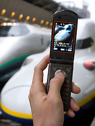 Person photographing bullet train with camera phone at Tokyo railway station