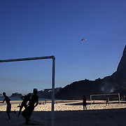 A Para glider prepares to land on the beach in the late afternoon light at Sao Conrado beach as locals play football on the beach, Rio de Janeiro,  Brazil. 8th July 2010. Photo Tim Clayton..The beaches of Rio de Janeiro, provide the ultimate playground for locals and tourists alike. Beach activity is in abundance as beach volley ball, football and a hybrid of the two, foot volley, are played day and night along the length and breadth of Rio's beaches. .Volleyball nets and football posts stretch along the cities coastline and are a hive of activity particularly at it's most famous beaches Copacabana and Ipanema. .The warm waters of the Atlantic Ocean provide the ideal conditions for a variety of water sports. Walkways along the edge of the beaches along with exercise stations and cycleways encourage sporting activity, even an outdoor gym is available at the Parque Do Arpoador overlooking the ocean. .On Sunday's the main roads along the beaches of Copacabana, Leblon and Ipanema are closed to traffic bringing out thousands of people of all ages to walk, run, jog, ride, skateboard and cycle more than 10 km of beachside roadway. .This sports mad city is about to become a worldwide sporting focus as they play host to the world's biggest sporting events with Brazil hosting the next Fifa World Cup in 2014 and Rio de Janeiro hosting the Olympic Games in 2016...