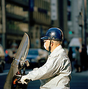 Man on a motorbike with a facemask to guard against pollution in Tokyo, Japan