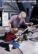 Active Aging Senior Citizens, Retired, Grandfather and Grandson Activities, Loving Relationship, Staying Young, Grandfather Repairs Bicycle